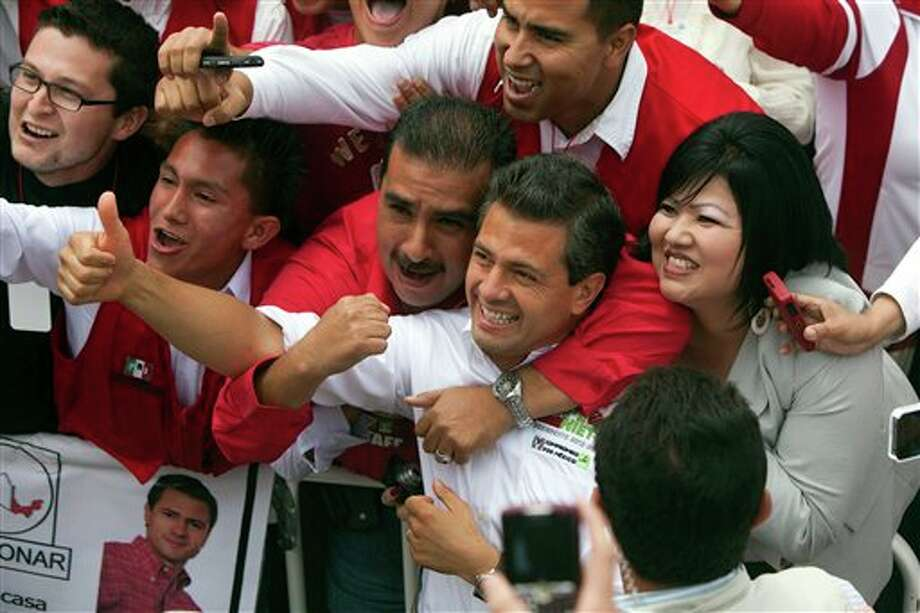 Mexican presidential candidate Enrique Pena Nieto of the Revolutionary Institutional Party (PRI), gives the thumbs up sign while being embraced by supporters during a  campaign stop in the northern border city of Tijuana, Mexico, Sunday, June 3, 2012. On July 1, Mexico will hold presidential elections. (AP Photo/Alex Cossio) Photo: Associated Press