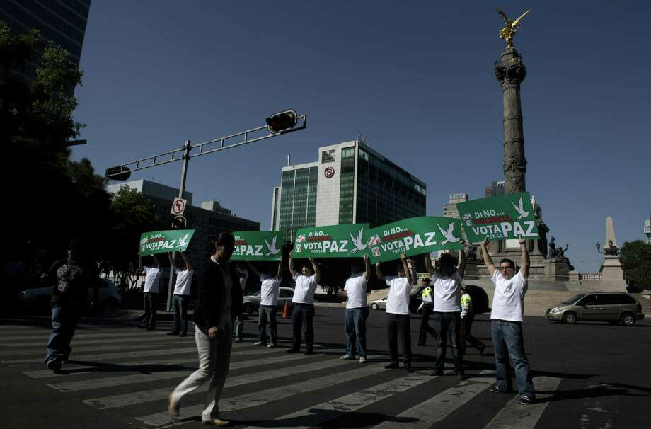 "Supporters of Mexican presidential candidate for the Institutional Revolutionary Party (PRI), Enrique Pena Nieto hold posters reading ""Say not to violence, vote for peace"" during a demonstration along Reforma Avenue in Mexico City on May 29, 2012. Mexico will hold elections next July 1.   AFP PHOTO/Yuri CORTEZ        (Photo credit should read YURI CORTEZ/AFP/GettyImages) Photo: YURI CORTEZ, Getty Images / 2012 AFP"