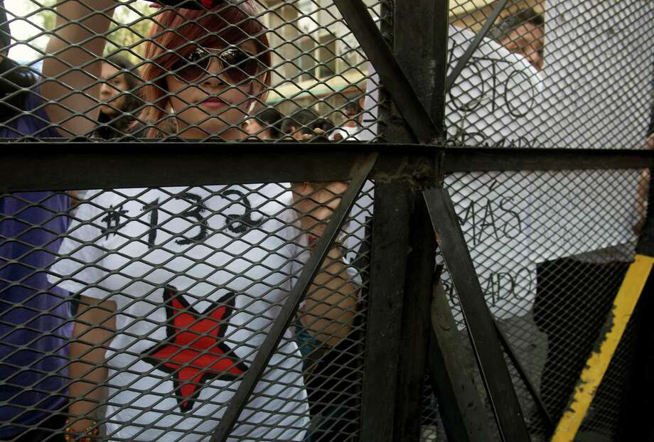 "Mexican university students, members of the new ""Yo soy 132"" (I am #132) movement, stand behind a security fence during a demonstration to demand the national simultaneous broadcast of the second debate of the four presidential candidates in the framework of the electoral campaign, in Mexico City on May 28, 2012. Mexico is to hold presidential elections next July 1st.   AFP PHOTO/Yuri CORTEZ        (Photo credit should read YURI CORTEZ/AFP/GettyImages) Photo: YURI CORTEZ, Getty Images / 2012 AFP"