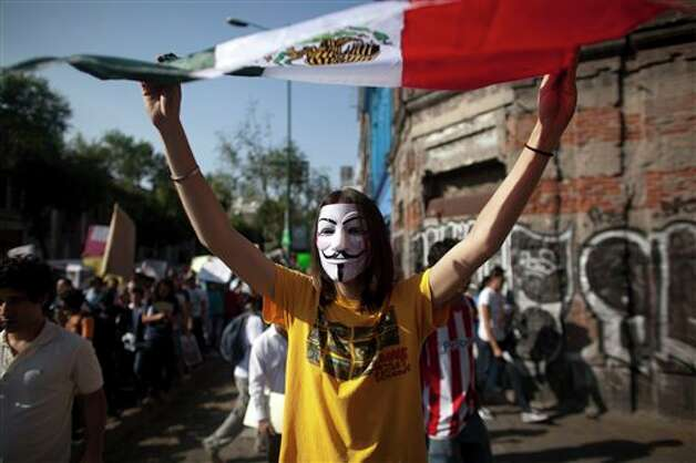 A demonstrator holds up a Mexico's national flag during a protest against a possible return of the old ruling Institutional Revolutionary Party (PRI) in Mexico City, Monday, May 28, 2012. Demonstrators also protested against what students perceive as a biased coverage by major Mexican TV networks of the presidential elections campaign, which they claim to be directed in favor of PRI's candidate Enrique Pena Nieto. Mexico will hold presidential elections on July 1. (AP Photo/Alexandre Meneghini) Photo: Associated Press