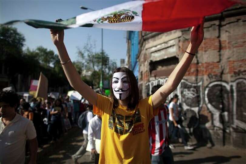 A demonstrator holds up a Mexico's national flag during a protest against a possible return of the o