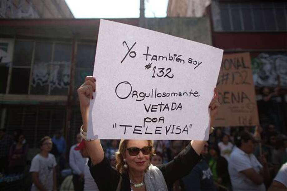 "A demonstrator holds up a sign during a protest against a possible return of the old ruling Institutional Revolutionary Party (PRI) in Mexico City, Monday, May 28, 2012. Demonstrators also protested against what students perceive as a biased coverage by major Mexican TV networks of the presidential elections campaign, which they claim to be directed in favor of PRI's candidate Enrique Pena Nieto. Mexico will hold presidential elections on July 1. The sign reads in Spanish ""I am also 132. Proudly vetoed by Televisa."" #132 is the name of a university movement that rejects the possible return of the Institutional Revolutionary Party (PRI). (AP Photo/Alexandre Meneghini) Photo: Associated Press"