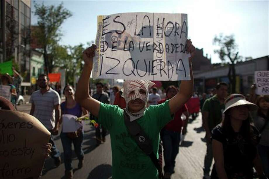 "A demonstrator holds a sign during a protest against a possible return of the old ruling Institutional Revolutionary Party (PRI) in Mexico City, Monday, May 28, 2012. Demonstrators also protested against what students perceive as a biased coverage by major Mexican TV networks of the presidential elections campaign, which they claim to be directed in favor of PRI's candidate Enrique Pena Nieto. Mexico will hold presidential elections on July 1. The sign reads in Spanish ""It's time for the real left."" (AP Photo/Alexandre Meneghini) Photo: Associated Press"