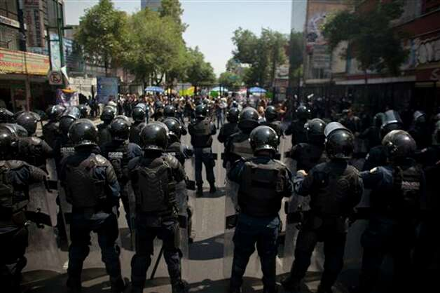 Police officers stand in front of protesters demonstrating against a possible return of the old ruling Institutional Revolutionary Party (PRI) in Mexico City, Monday, May 28, 2012. Demonstrators also protested against what students perceive as a biased coverage by major Mexican TV networks of the presidential elections campaign, which they claim to be directed in favor of PRI's candidate Enrique Pena Nieto. Mexico will hold presidential elections on July 1. (AP Photo/Alexandre Meneghini) Photo: Associated Press