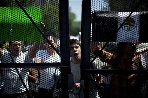 A man shouts slogans through a fence placed by police during a demonstration against a possible return of the old ruling Institutional Revolutionary Party (PRI) in Mexico City, Monday, May 28, 2012. Demonstrators also protested against what they perceive as a biased coverage by major Mexican TV networks of the presidential elections campaign, which they claim to be directed in favor of PRI's candidate Enrique Pena Nieto. Mexico will hold presidential elections on July 1. (AP Photo/Alexandre Meneghini) Photo: Associated Press