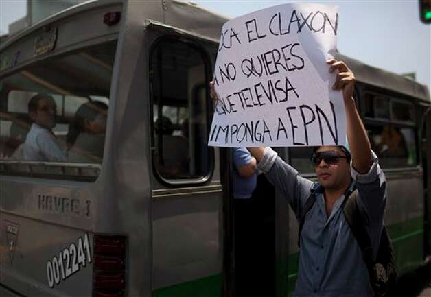 "A demonstrator holds up a sign during a protest against a possible return of the old ruling Institutional Revolutionary Party (PRI) in Mexico City, Monday, May 28, 2012. Demonstrators also protested against what students perceive as a biased coverage by major Mexican TV networks of the presidential elections campaign, which they claim to be directed in favor of PRI's candidate Enrique Pena Nieto. Mexico will hold presidential elections on July 1. The sign reads in Spanish ""Touch the klaxon if you don't want that Televisa impose Enrique Pena Nieto."" (AP Photo/Alexandre Meneghini) Photo: Associated Press"