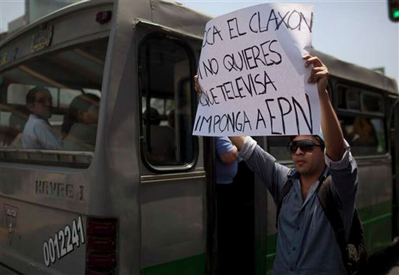 A demonstrator holds up a sign during a protest against a possible return of the old ruling Institut