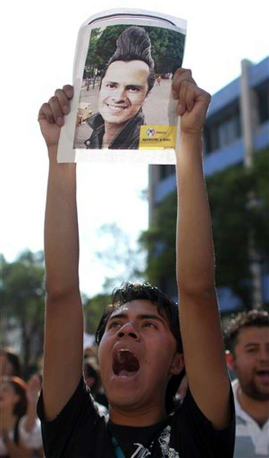 A protester shouts slogans during a protest against a possible return of the old ruling Institutional Revolutionary Party (PRI) in Mexico City, Monday, May 28, 2012. Demonstrators also protested against what students perceive as a biased coverage by major Mexican TV networks of the presidential elections campaign, which they claim to be directed in favor of PRI's candidate Enrique Pena Nieto. Mexico will hold presidential elections on July 1. The image represents Pena Nieto. (AP Photo/Alexandre Meneghini) Photo: Associated Press