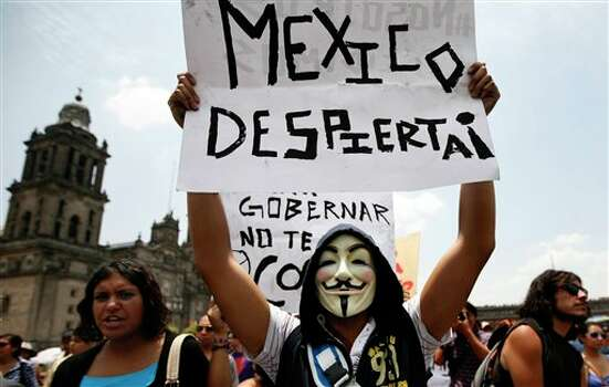 "A man wearing a mask holds up a sign that reads in Spanish ""Wake up Mexico"" during a protest against the possible return of the old ruling Institutional Revolutionary Party (PRI) in Mexico City, Sunday, June 3, 2012. Mexico will hold presidential elections on July 1. (AP Photo/Marco Ugarte) Photo: Associated Press"