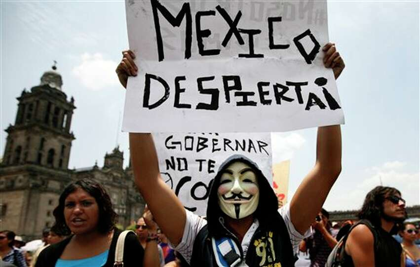 A man wearing a mask holds up a sign that reads in Spanish
