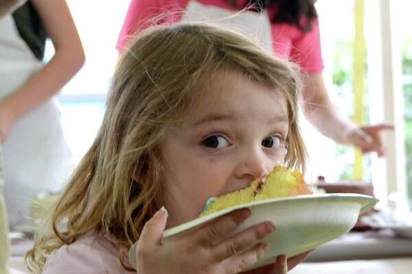 Three-year-old Zara Maggard has a bite of her cake at the Ice Cream Social on Sunday, June 3, 2012.  New Canaan, Conn.