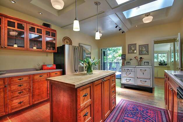 The updated kitchen features a butcher block island and Corian counters. Photo: Patrice Jerome