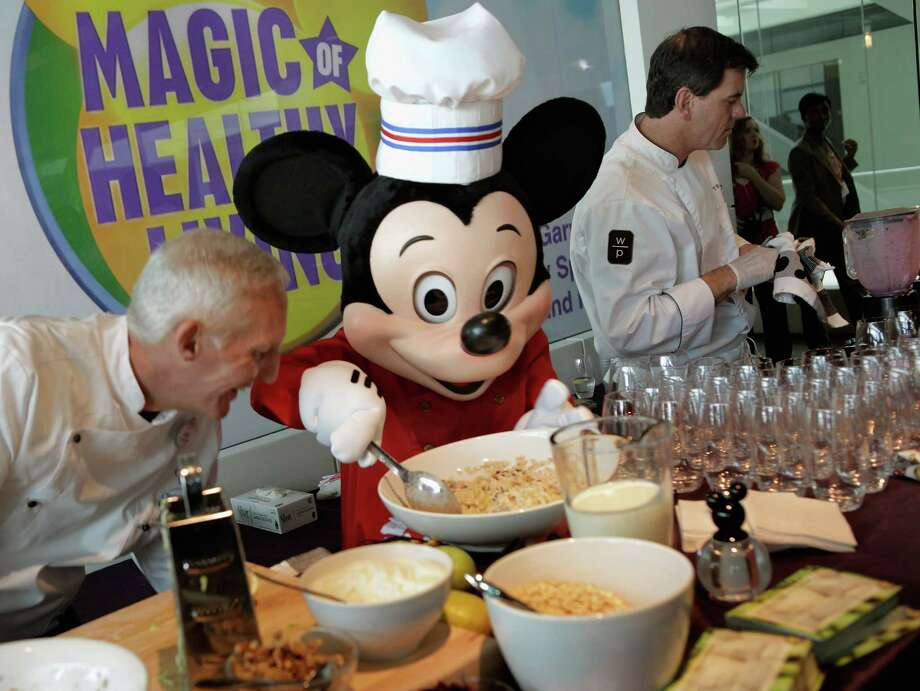 "A Mickey Mouse character assists Walt Disney Parks and Resorts Culinary Dietary Specialist Gary Jones (L) make healthy smoothies during an event introducing Disney's new ""Magic of Healthy Living"" program at the Newseum June 5, 2012 in Washington, DC. As part of the new healthy eating initiative, all products advertised on Disney's child-focused television channels, radio stations and Web sites must adhear to a new set of strict nutritional standards. Addionally, Disney-licensed products that meet criteria for limited calories, saturated fat, sodium and sugar can display a logo - Mickey Mouse ears and a check mark - on their packaging. Photo: Chip Somodevilla, Getty Images / 2012 Getty Images"