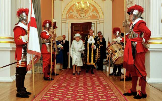 Queen Elizabeth II walks with David Wooton the Lord Mayor of London, after arriving AT Mansion House, in the City of London, for a reception hosted by the Lord Mayor of London and the City in honour of her Diamond Jubilee in London on June 5, 2012. Britain's Queen Elizabeth II wraps up four days of diamond jubilee celebrations and festivities will conclude with a ceremonial carriage procession in London, a formal contrast to the spectacular pop tribute staged outside Buckingham Palace the day before. AFP PHOTO /JOHN STILLWELL / POOL        (Photo credit should read JOHN STILLWELL/AFP/GettyImages) Photo: JOHN STILLWELL, AFP/Getty Images / 2012 AFP