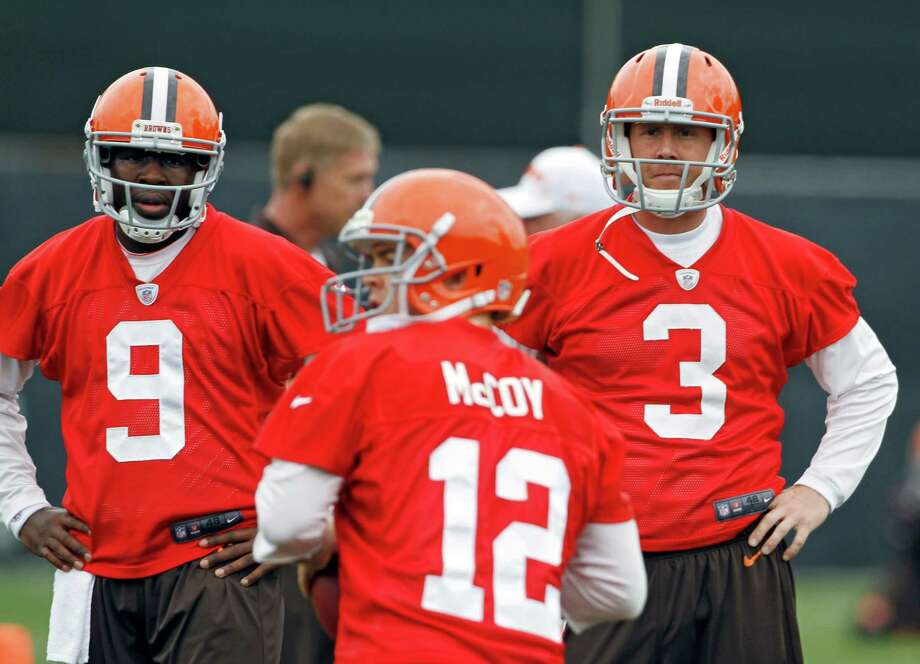 Thaddeus Lewis (left) and rookie Brandon Weeden (right) look on as fellow QB Colt McCoy during the team's practice Tuesday. Photo: AP