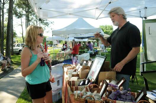Katie Orth, from left, of Kingwood, talks to Craig Stewart, of Chapel Hill, about his Lavenda mosquito spray during the Kingwood Farmer's Market in Town Center Park. Photo: Jerry Baker