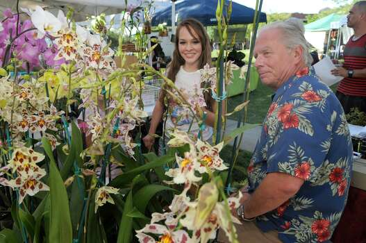 Jenny Estrada, of Kingwood, checks out the flowers at the Orchid Obsession booth, owned by Bruce Cameron, of Spring, during the Kingwood Farmer's Market in Town Center Park. Photo: Jerry Baker
