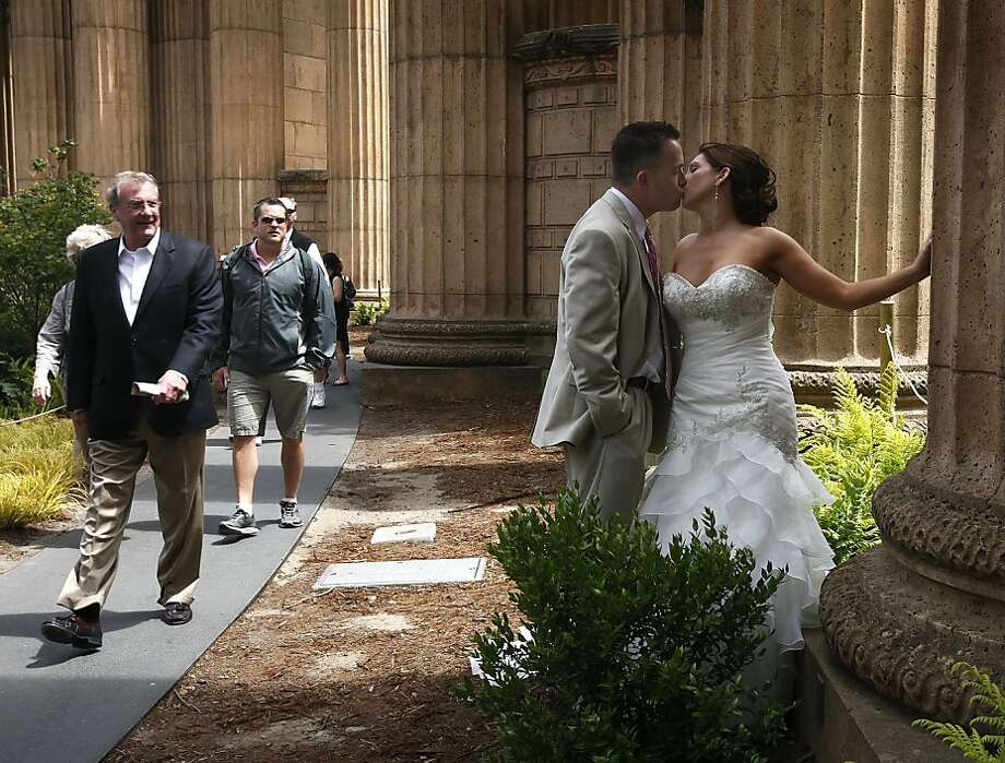 Visitors to the Palace of Fine Arts watch newlyweds Joshua and Leah Smalley pose for their wedding photos in San Francisco, Calif. on Saturday, June 2, 2012. Photo: Paul Chinn, The Chronicle