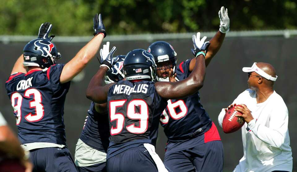 Houston Texans defenders Jared Crick (93), Whitney Merciless (59) and Tim Jamison (96) charge in on
