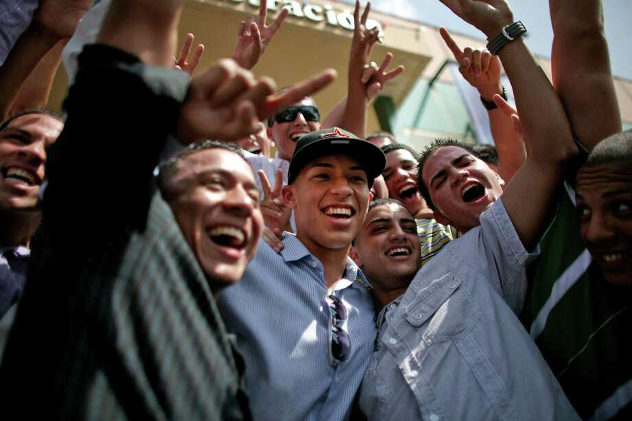 Student and baseball player Carlos Correa, center, is surrounded by classmates upon his arrival to the Puerto Rico Baseball Academy High School in Caguas, Puerto Rico, Tuesday, June 5, 2012. Correa, the 17-year-old slugging shortstop made hometown history on Monday after being selected by the Houston Astros as No. 1 in the Major League Baseball draft, becoming the first No. 1 overall pick from Puerto Rico. (AP Photo/Ricardo Arduengo) Photo: Ricardo Arduengo, Associated Press / AP