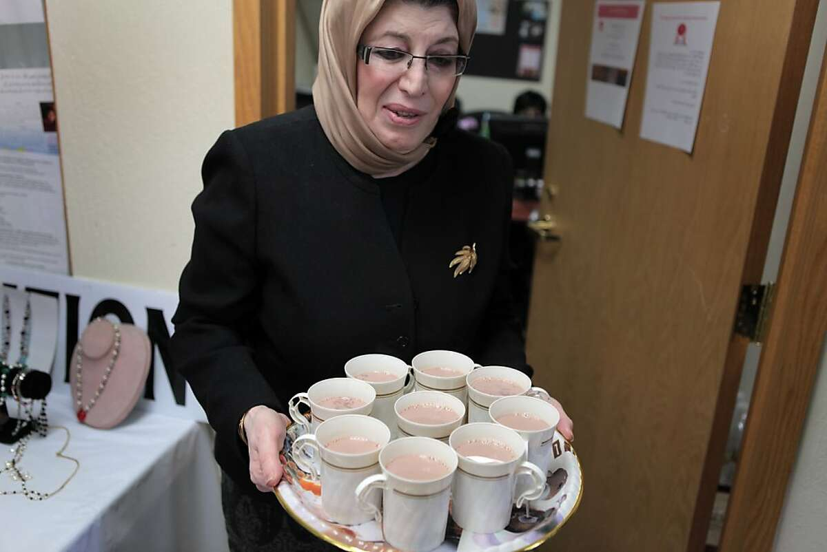 Mariam Mogaddedi, a volunteer at the Afghan Coalition, offers visitors with a delegation from Afghanistan tea after a meeting on Tuesday, April 17, 2012 in Fremont, Calif.