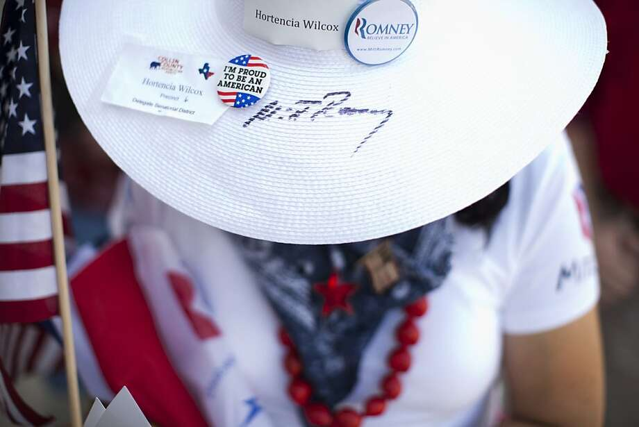 Hortencia Wilcox of Allen, Texas wears a hat signed by Republican presidential candidate, former Massachusetts Gov. Mitt Romney while waiting in line at a campaign stop at Southwest Office Systems on Tuesday, June 5, 2012 in Fort Worth, Texas.  (AP Photo/Evan Vucci) Photo: Evan Vucci, Associated Press