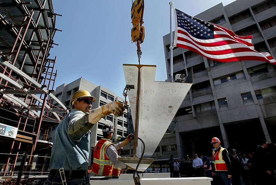 Irons worker Nick Grey guides the bean as they prepare to lift the final beam into place, as San Francisco General Hospital celebrates a milestone in the rebuild of it's care facility with the topping out ceremony  on Tuesday June 5, 2012, in San Francisco, Ca. Photo: Michael Macor, The Chronicle