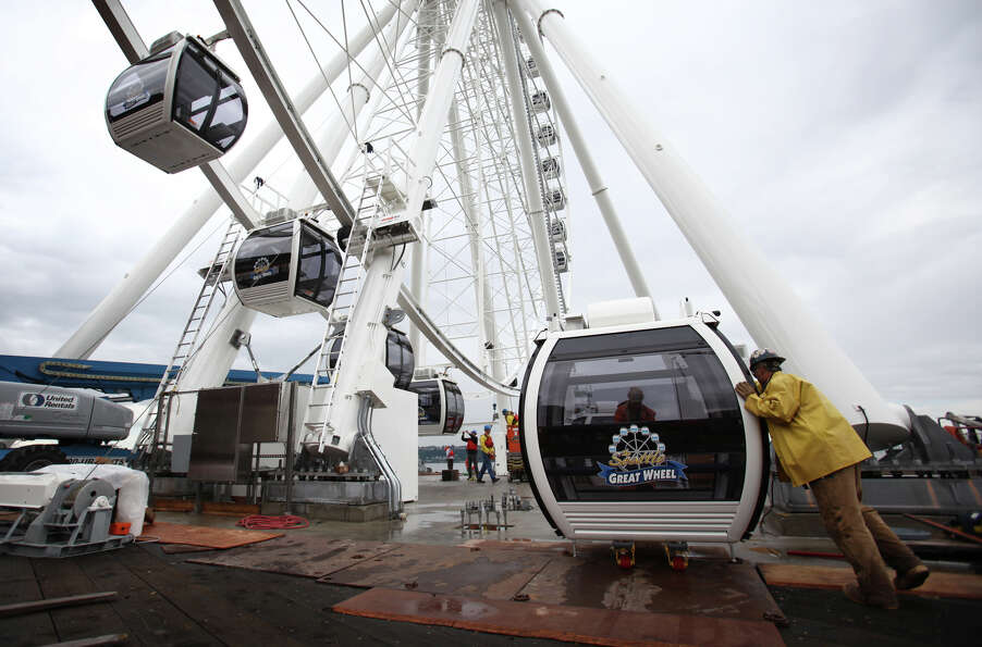 A worker guides a gondolas into place under the Seattle 'Great Wheel' on Tuesday, June 5, 2012.  The