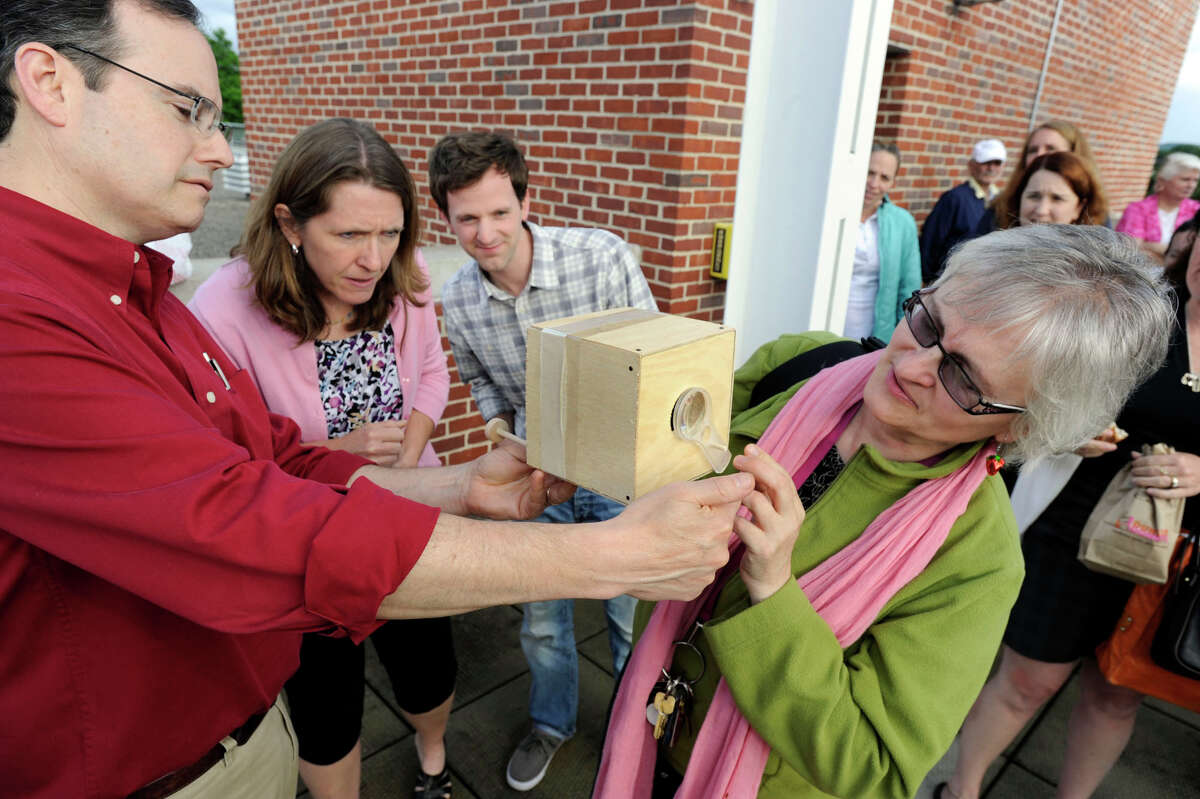 Peter Bernson, left, a teacher at Reed Intermediate School, brought a camera obscura to the roof of the Science Building at Western Connecticut State University, where people gathered Tuesday evening, June 5, 2012, to view the Transit of Venus. Also photographed from left center are, Kris Feda, Todd Stentiford and Carolann Lutz.