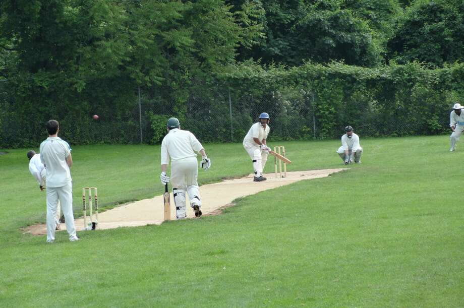 Members of the Greenwich-based Mad Dogs Cricket Club play the game they love on a recent weekend afternoon. Here a bowler (pitcher) let's one fly as the batsman (batter) prepares to swing. Photo: Contributed Photo