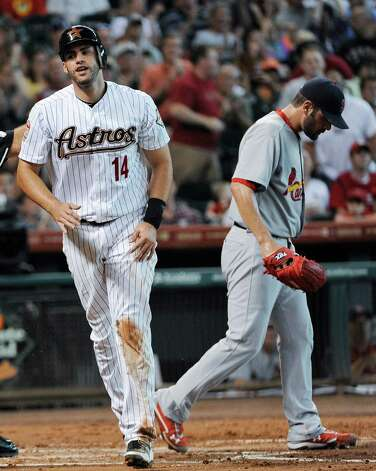 Houston Astros' J.D. Martinez (14) scores as St. Louis Cardinals pitcher Jaime Garcia, right, walks back to the mound in the first inning of a baseball game Tuesday, June 5, 2012, in Houston. Martinez scored with the bases loaded on a Garcia wild pitch. Photo: AP