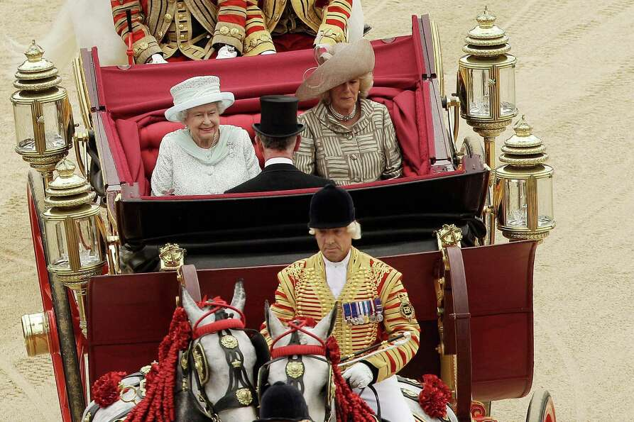 Queen Elizabeth II (L) makes her way by carriage with Camilla, Duchess of Cornwall and Prince Charle