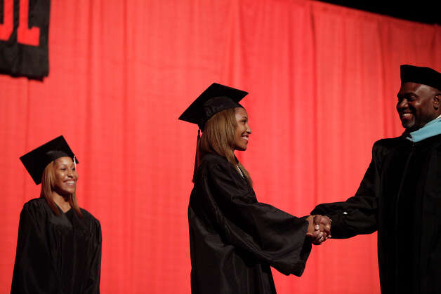 Aundrea Davis (left) watches as her twin sister, Adriane Davis, shakes the hand of Dr. Willis Mackey, superintendent of the Judson Independent School District, as they walk across the stage during Wagner High School's graduation at the Alamodome on Tuesday, June 5, 2012. Photo: Lisa Krantz, San Antonio Express-News / 2012 San Antonio Express-News