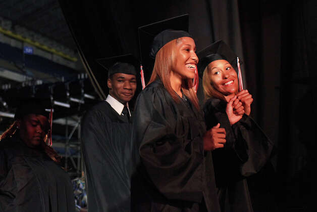 Aundrea Davis, 18, and her twin sister, Adriane Davis (right), share a fist bump backstage as they wait to walk across the stage during Wagner High School's graduation at the Alamodome on Tuesday, June 5, 2012. Photo: Lisa Krantz, San Antonio Express-News / 2012 San Antonio Express-News