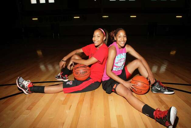 Adriane (left) and Aundrea Davis are preparing for the challenge of not being together for the first time in their lives. They'll be attending Texas colleges about 500 miles apart. Photo: Helen L. Montoya, San Antonio Express-News / ©SAN ANTONIO EXPRESS-NEWS