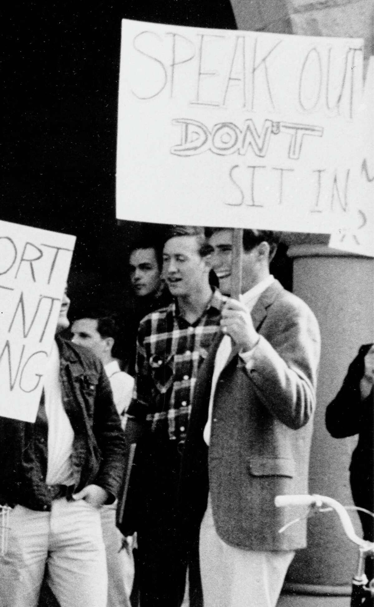 In this 1966 photo taken by a photographer at the San Francisco Examiner newspaper, 19-year-old Mitt Romney, right, then a student at Stanford University, participates in a counter-protest on campus. Romney and his fellow students were reacting to a protest then being waged by other students upset with the university's student draft deferment policies. Romney sought and received four draft deferments from 1965 to 1970 during college and his time as a Mormon missionary in France. The country was cutting troop levels by the time he became eligible for service, and his draft number was not called. (AP Photo/San Francisco Examiner)