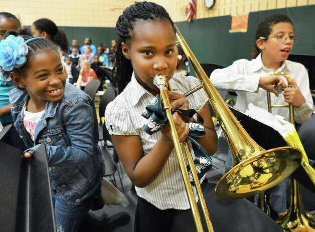 Philip J. Schuyler Achievement Academy concert band member Latia Allah,center, tries out a new trombone, one of $20,000 worth of musical instruments donated by Fidelity Investments? new Albany Investor Center during a ceremony at the school in Albany Tuesday June 5, 2012.   (John Carl D'Annibale / Times Union) Photo: John Carl D'Annibale / 00017720B