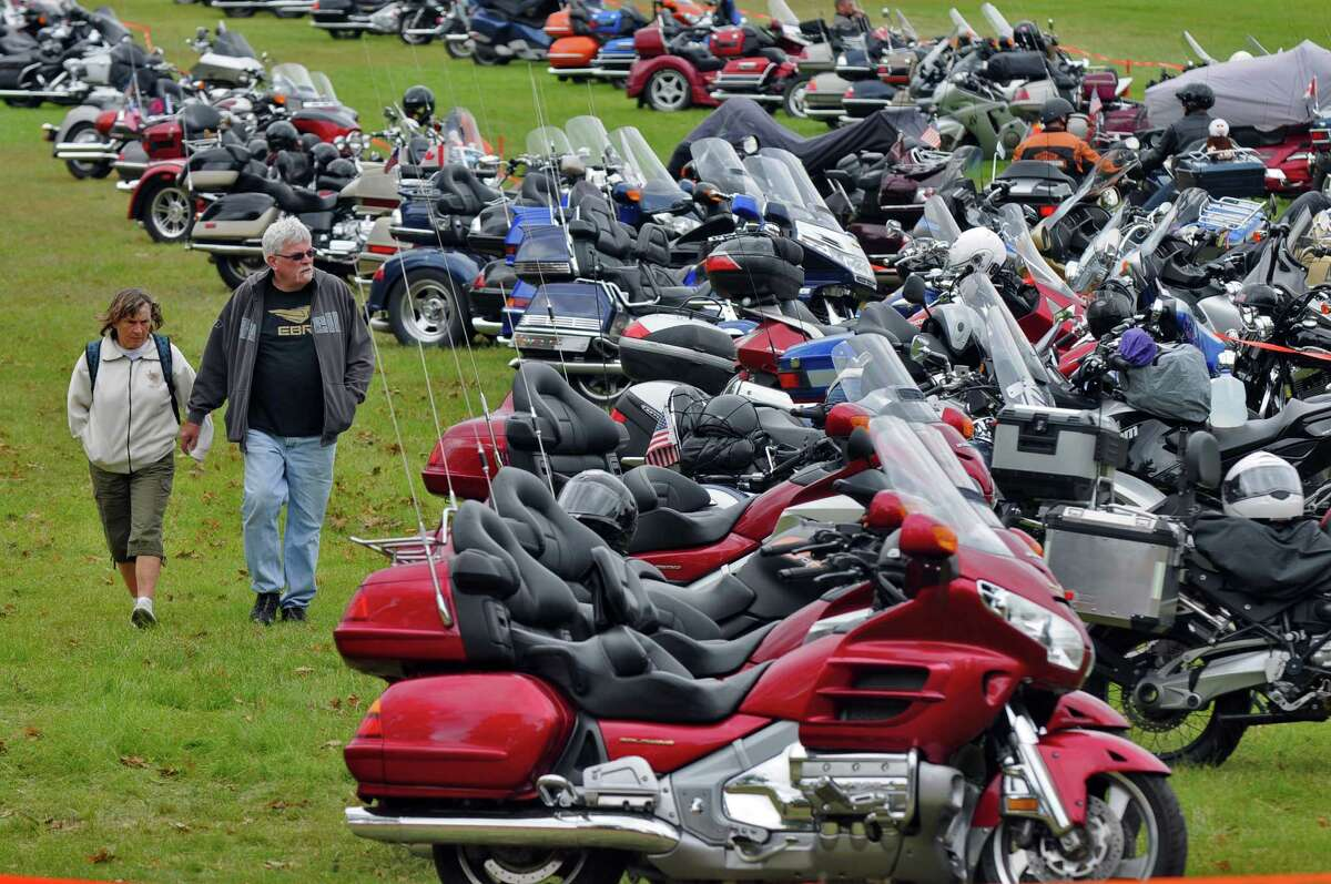 Bobbi and David Reeves of Peru, NY walk past motorcycles parked in Lake George Battlefield State Park for the start of the annual Americade, on Tuesday June 5, 2012 in Lake George, NY. The parking donations for the parking lot were to benefit the Prospect Child and Family Center, of Queensbury. (Philip Kamrass / Times Union )