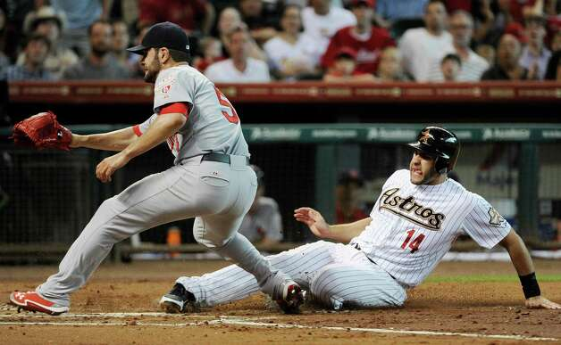 Houston Astros' J.D. Martinez (14) scores as St. Louis Cardinals pitcher Jaime Garcia (54) waits for the ball in the first inning of a baseball game Tuesday, June 5, 2012, in Houston. Martinez scored with the bases loaded on a Garcia wild pitch. Photo: AP