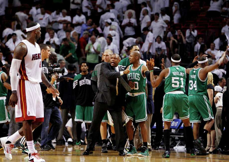 Boston Celtics head coach Doc Rivers, center, celebrates with Ray Allen (20), Keyon Dooling (51) and Paul Pierce (34) as Miami Heat's LeBron James, left, walks past during the second half of Game 5 in their NBA basketball Eastern Conference Finals playoff series, Tuesday, June 5, 2012, in Miami. The Celtics won 94-90. (AP Photo/Lynne Sladky) Photo: Associated Press / AP