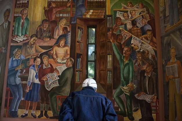 "Diony Arellano reads about the murals painted in the foot of Coit Tower on Tuesday, June 5, 2012 in San Francisco, Calif. ""We must protect this landmark,"" Arellano said. Coit tower was built in 1933 following Lillie Hitchcock Coit's will donating one-third of her estate to the city for civic beautification. Photo: Dania Maxwell, Special To The Chronicle"