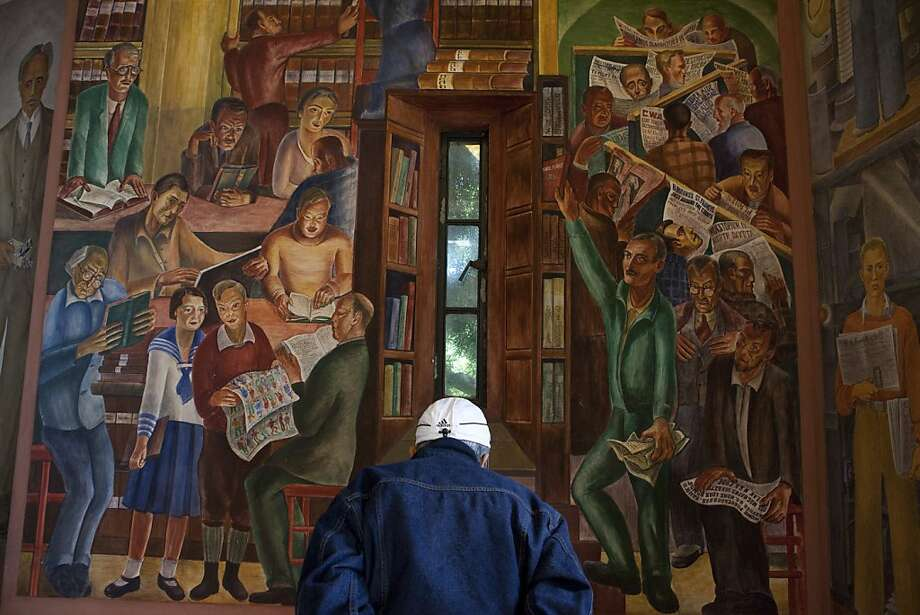 """Diony Arellano reads about the murals painted in the foot of Coit Tower on Tuesday, June 5, 2012 in San Francisco, Calif. """"We must protect this landmark,"""" Arellano said. Coit tower was built in 1933 following Lillie Hitchcock Coit's will donating one-third of her estate to the city for civic beautification. Photo: Dania Maxwell, Special To The Chronicle"""