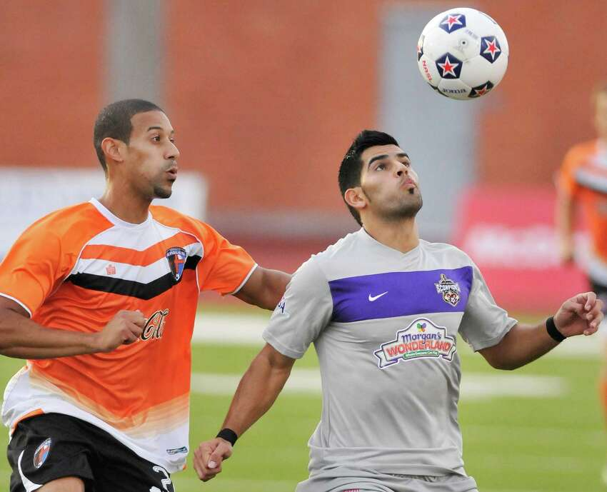 The Scorpions' Esteban Bayona, right, heads the ball ahead of Charlotte's Devon Grousis during a U.S. Open Cup soccer match, Tuesday, June 5, 2012, at Heroes Stadium.