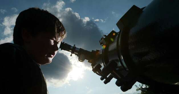 Carson Clemmons looks through a telescope at the planet Venus as it transits across the the sun Tuesday, June 5, 2012, in the parking lot at Decatur Heritage Christian School in Decatur, Ala. This is the last transit of Venus viewable from Earth for over 100 years. Photo: The Decatur Daily, Gary Cosby Jr.
