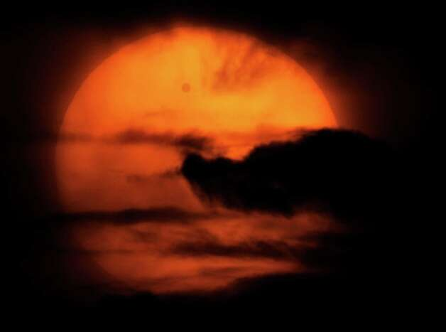 Venus is seen passing in front of the sun in the clouds, in this image taken through a telescope, from Losevo village, north of St. Petersburg, Russia, Wednesday, June 6, 2012. People around the world turned their attention to the daytime sky on Tuesday and early Wednesday in Asia to make sure they caught the rare sight of the transit of Venus. Photo: Dmitry Lovetsky