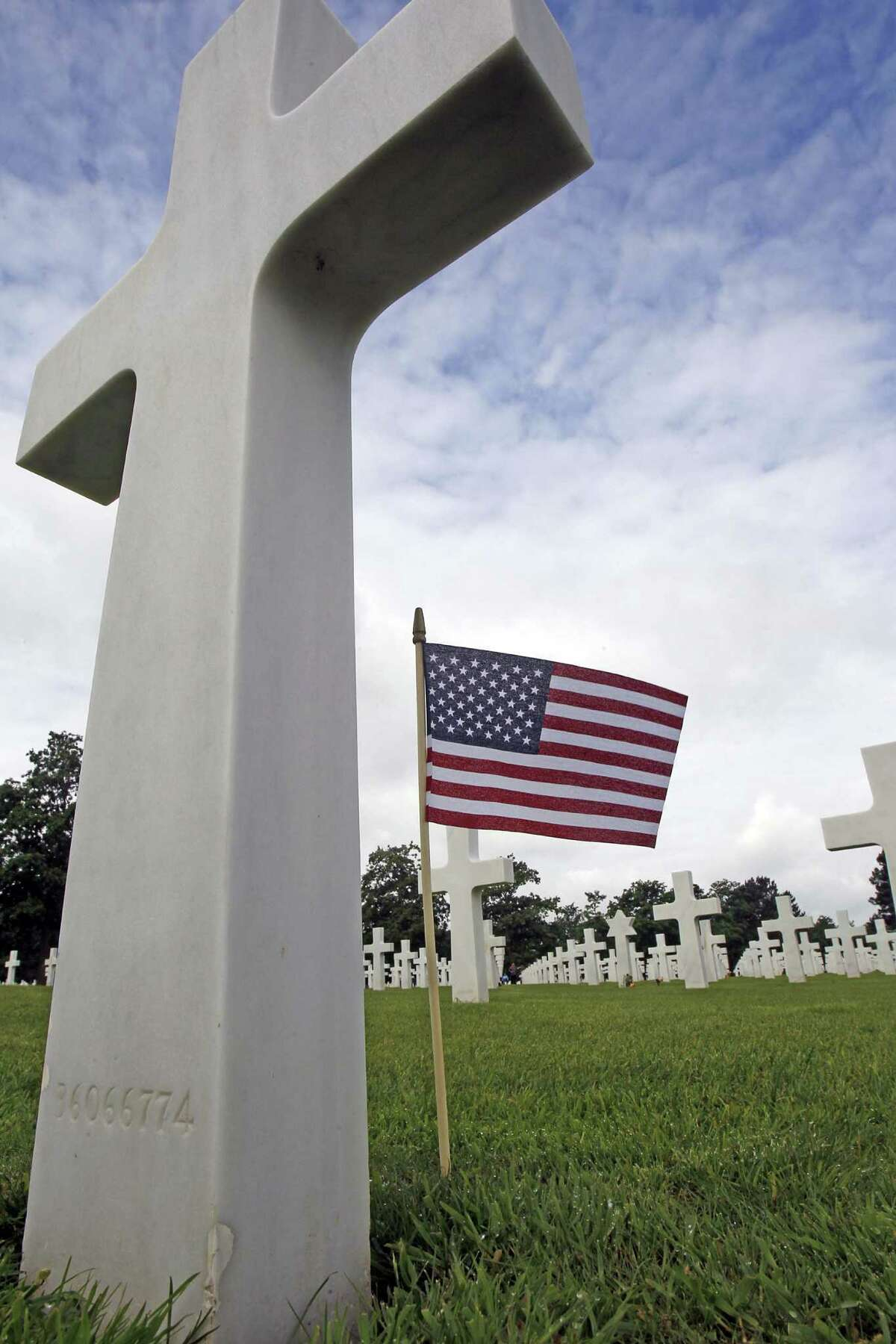 A U.S. flag flies between graves at the Colleville American military cemetery, in Colleville sur Mer, western France, Wednesday June 6, 2012, as part of the commemoration of the 68th anniversary of D-Day.(AP Photo/Remy de la Mauviniere)
