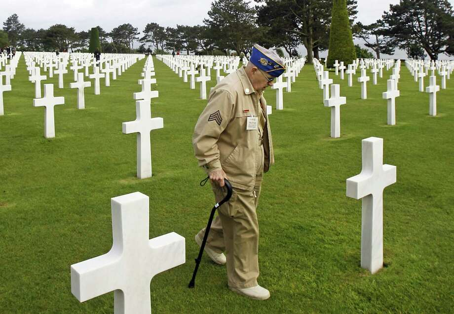 U.S. WW II veteran Clarence  Mac Evans, 87, from West Virginia, who landed in Normandy on June 6, 1944, with the 29th infantery division, walks among the graves at the Colleville American military cemetery, in Colleville sur Mer, western France, Wednesday  June 6, 2012, before the start of the ceremony commemorating the 68th anniversary of the D-Day. Clarence MacEvans is searching  for the tombs of 17 of his fellows who died on  D Day.(AP Photo/Remy de la Mauviniere) Photo: Remy De La Mauviniere, Associated Press / AP