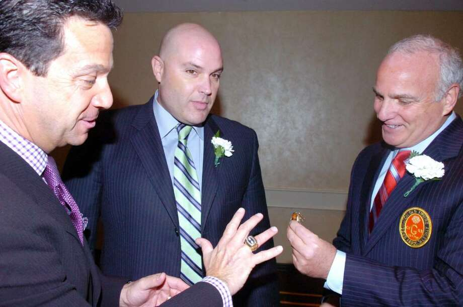 Former Giants punter Sean Landeta's Super Bowl rings lure Bill Evans, left, and President of the Old Timers Club John Carlucci at the Annual Old Timers Dinner at the Greenwich Hyatt Regency Tuesday evening, Nov. 24, 2009. Landeta was one of this year's honorees. Photo: Keelin Daly / Greenwich Time
