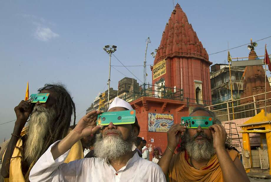 Hindu holy men use special cardboard eclipse glasses as they watch the transit of Venus on the banks of the Ganges River in Varanasi, India, Wednesday, June 6, 2012. People around the world turned their attention to the daytime sky on Tuesday and early Wednesday in Asia to make sure they caught the rare sight of the transit of Venus. (AP Photo/Rajesh Kumar Singh) Photo: Rajesh Kumar Singh, Associated Press