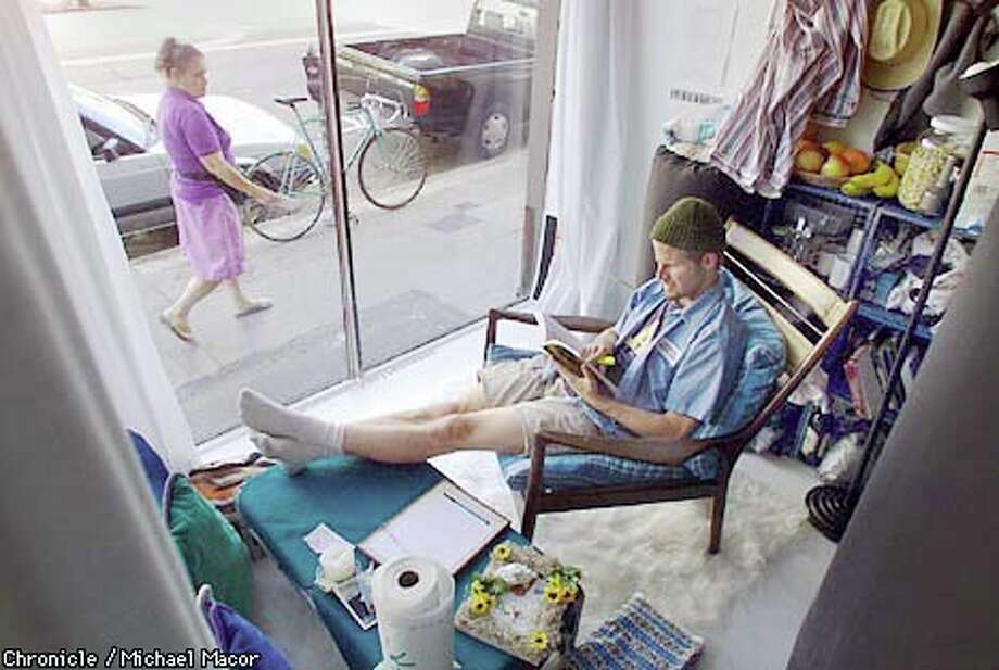 """John Fanning relaxed in the living quarters he set up in the storefront of Artists Television Access in August for an exhibition called """"Consumption: How Much Do We Really Need.'' Fanning's project is part of  """"Art Strikes Back,'' a series by San Francisco artists protesting gentrification in the Mission District. Chronicle photo by  Michael Macor"""